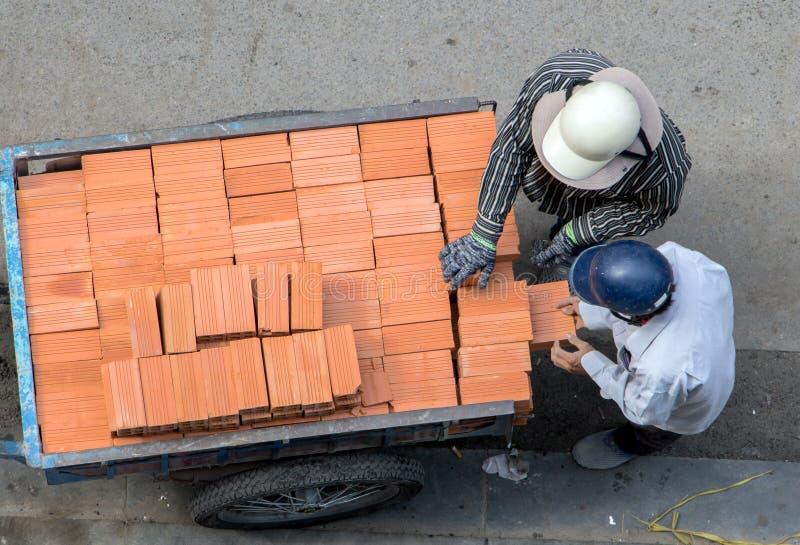 O trabalhador leva tijolos de um carro na bicicleta imagens de stock royalty free