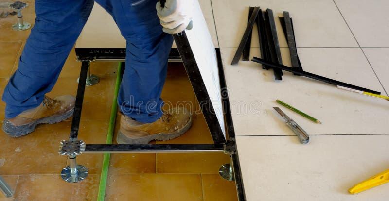 O trabalhador leva um assoalho de flutuação nos pés de aço foto de stock