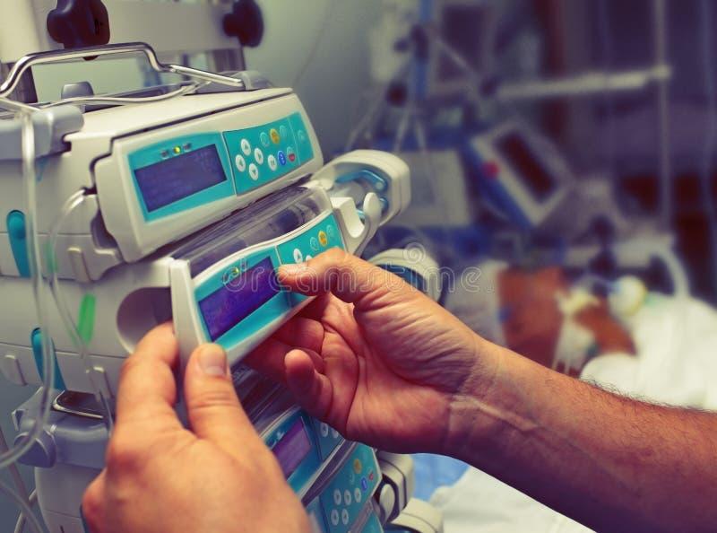 O trabalhador médico configura o equipamento em ICU imagem de stock