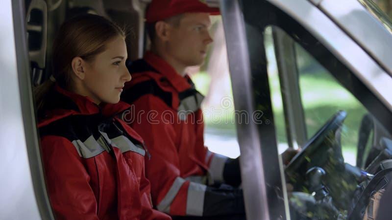 O trabalhador médico da emergência que senta-se no carro, profissionais no dever fornece primeiros socorros fotografia de stock