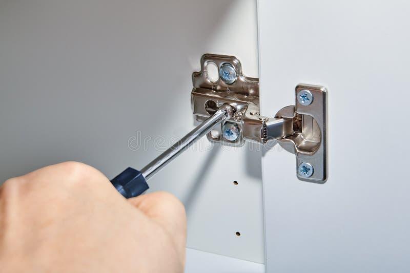 O trabalhador manual ajusta as dobradiças na porta da tabela do escritório fotos de stock