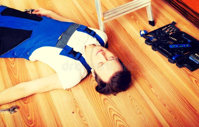 O trabalhador manual novo caiu de uma escada e das mentiras no assoalho fotos de stock