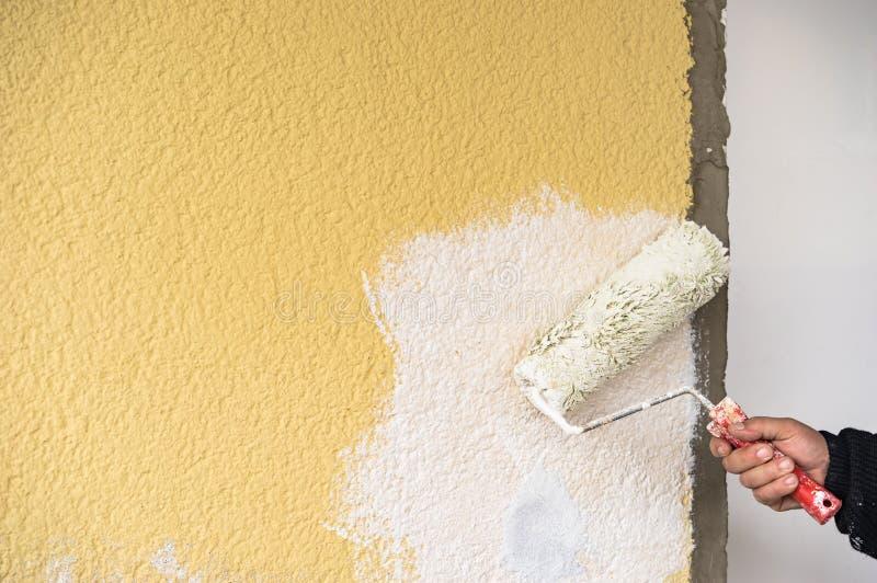 O trabalhador manual pinta o branco com rolo do pintor, close-up da parede fotos de stock