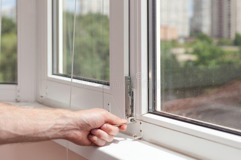 O trabalhador manual repara a janela plástica com um hexágono O trabalhador ajusta a operação da janela plástica fotografia de stock