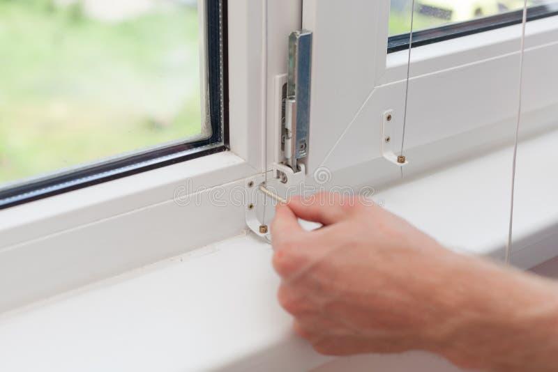 O trabalhador manual repara a janela plástica com um hexágono O trabalhador ajusta a operação da janela plástica imagens de stock
