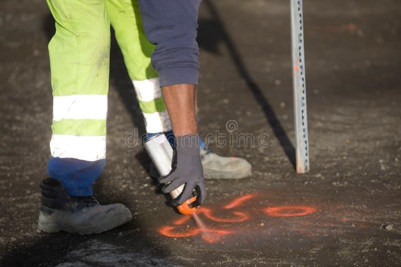 O trabalhador marca um ponto no asfalto com pintura à pistola fluorescente foto de stock