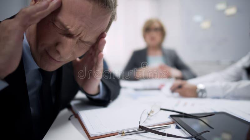 O trabalhador masculino tem o ataque da enxaqueca causado pelo esforço e pela exaustão no local de trabalho imagens de stock