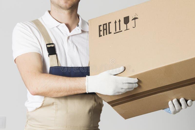 O trabalhador movente do serviço guarda o close-up da caixa de cartão Motor no pacote guardando uniforme nas mãos O internamento  fotografia de stock royalty free