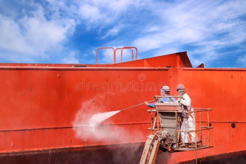 O trabalhador na altura polvilha perto a limpeza da água do jato imagem de stock