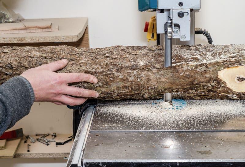 O trabalhador na oficina da carpintaria corta o log nas placas que usam uma faixa viu joinery Ofícios de madeira de madeira crus  foto de stock royalty free