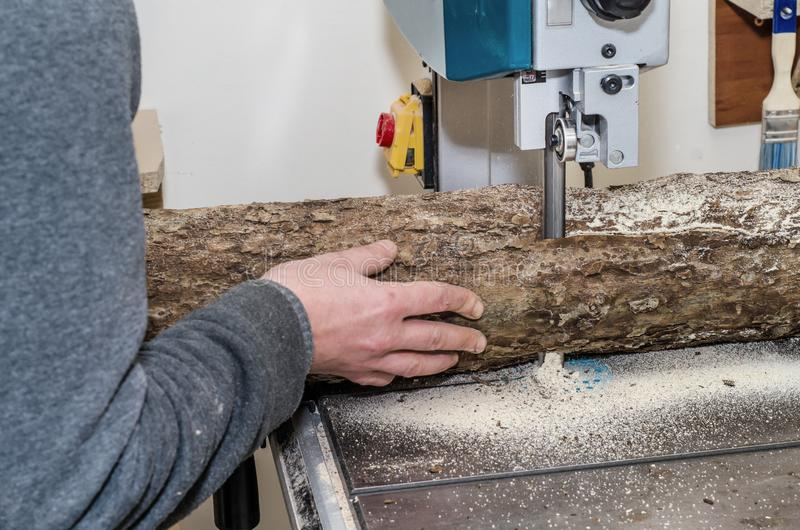 O trabalhador na oficina da carpintaria corta o log nas placas que usam uma faixa viu joinery Ofícios de madeira de madeira crus  fotos de stock royalty free