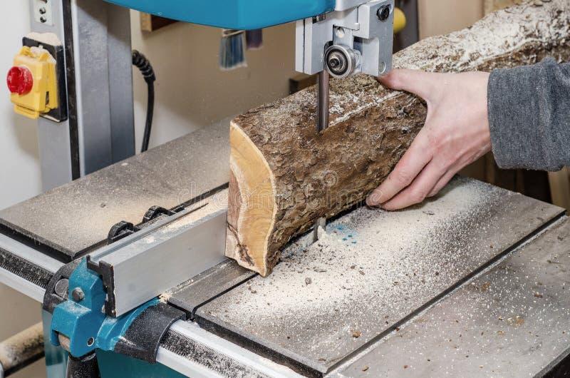 O trabalhador na oficina da carpintaria corta o log nas placas que usam uma faixa viu joinery Ofícios de madeira de madeira crus  fotografia de stock