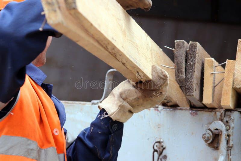 o trabalhador nas luvas está carregando pranchas no caminhão fotos de stock royalty free
