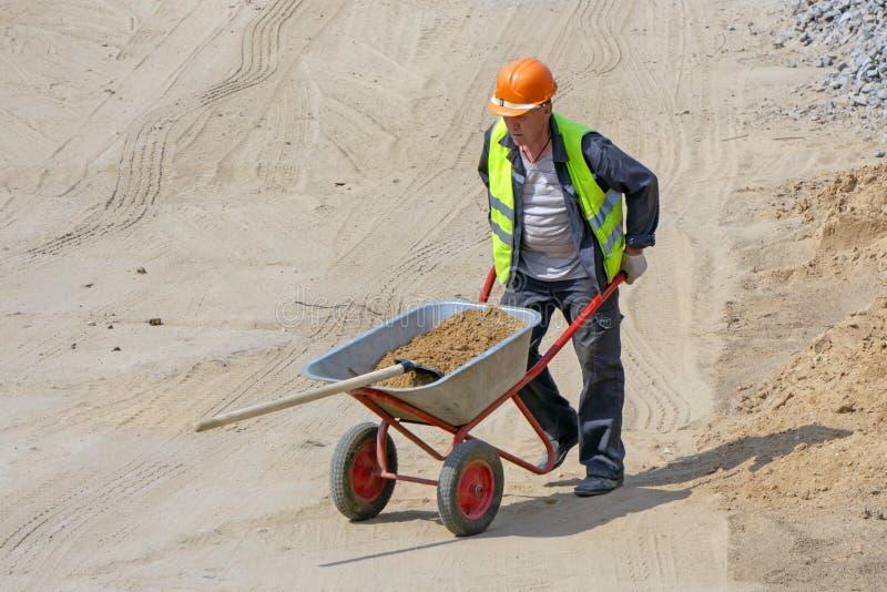 O trabalhador no canteiro de obras carrega a pá com a areia no carrinho de mão fotos de stock