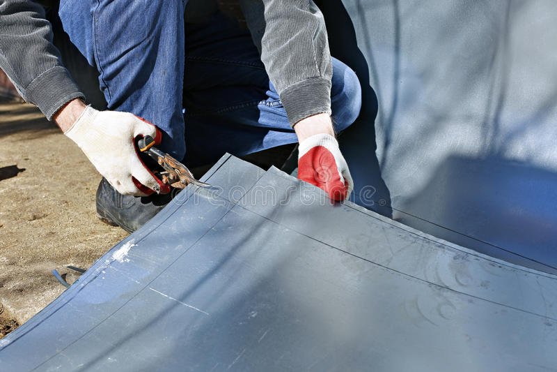 O trabalhador no canteiro de obras cortou tesouras de aço inoxidável da folha do corte do metal foto de stock