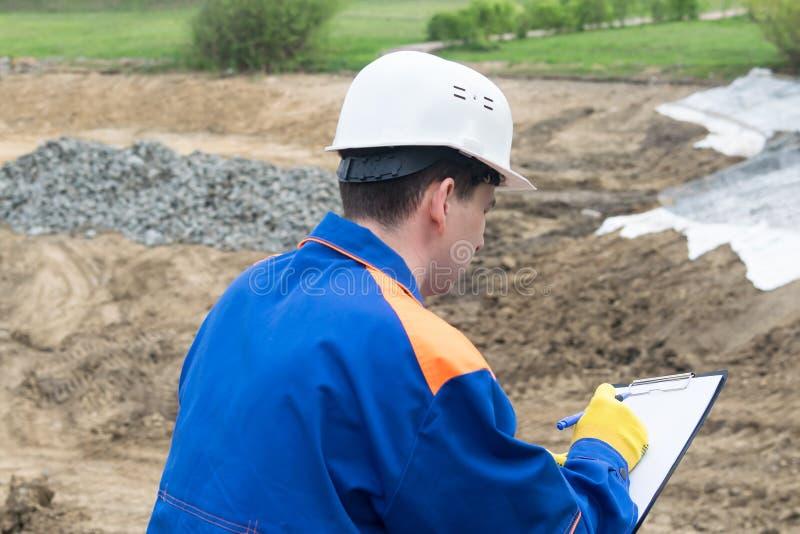 O trabalhador no local de construção faz anotações no tablet, visão traseira fotos de stock