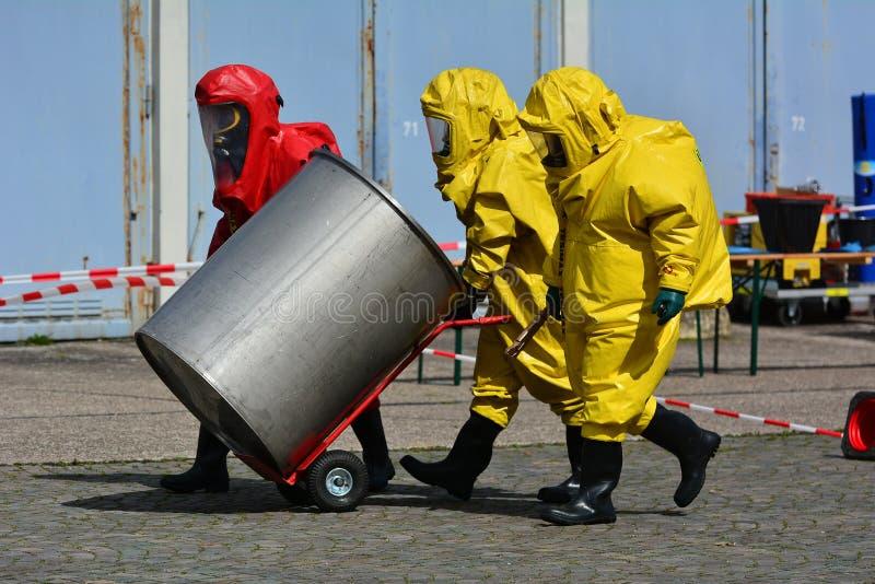 O trabalhador no uniforme protetor, a máscara, as luvas e as botas transportam tambores dos produtos químicos fotografia de stock