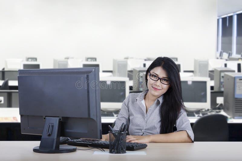 O trabalhador novo olha seguro com computador imagem de stock