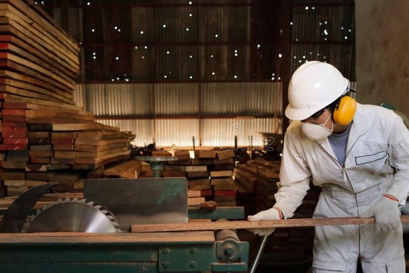 O trabalhador novo profissional no uniforme branco e no equipamento de segurança que cortam uma parte de madeira na tabela viu a  foto de stock