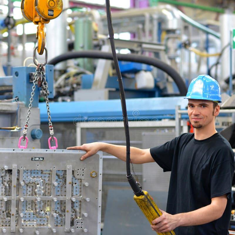 O trabalhador opera um guindaste em uma planta industrial - interior em um f fotografia de stock