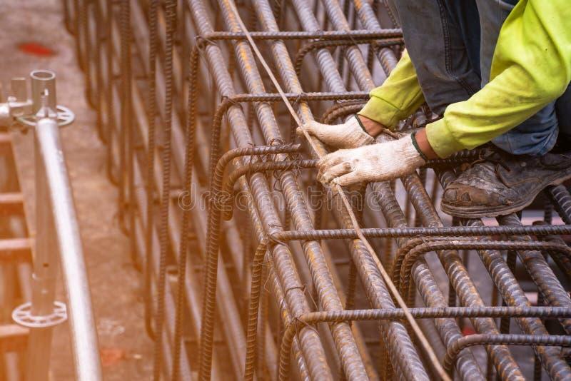 O trabalhador pôs a camisa verde da segurança, usa um ferro macio, amarra um grande fio de aço na área que está construindo uma g fotografia de stock