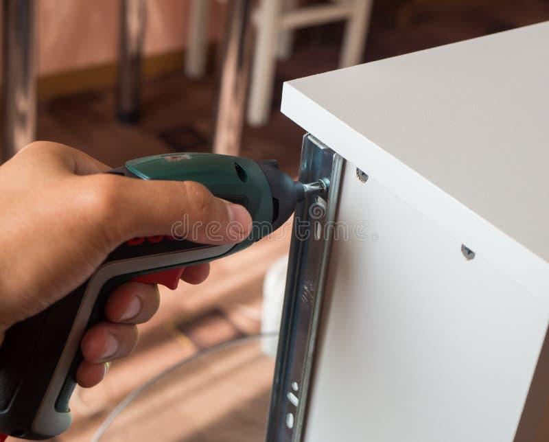 O trabalhador parafusa os trilhos da mobília à caixa da mobília Tiro do close up DIY imagens de stock royalty free