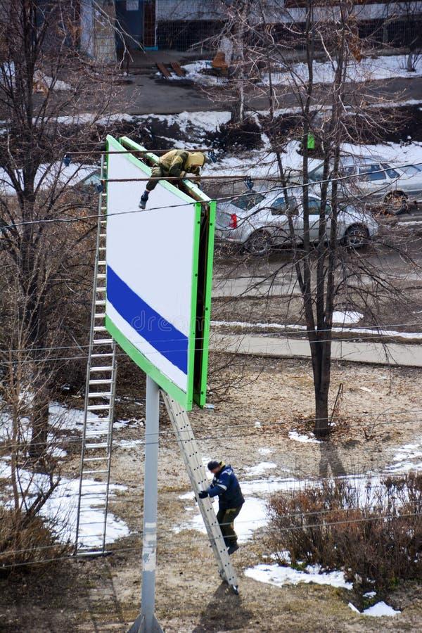 O trabalhador prepara o quadro de avisos a instalar a propaganda nova Montanhista industrial que trabalha em uma escada - colocan imagem de stock