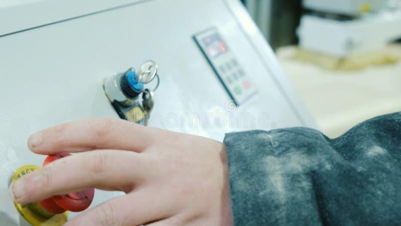 O trabalhador pressiona a tecla 'Iniciar Cópias' em uma máquina moderna do woodworking do CNC, close-up foto de stock royalty free