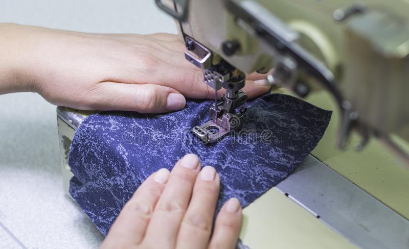 O trabalhador que costura a produção ajusta a máquina de costura fotografia de stock royalty free