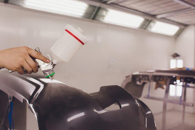 O trabalhador que pinta uma placa do preto do carro parte na garagem especial, no traje vestindo e na engrenagem protetora fotos de stock