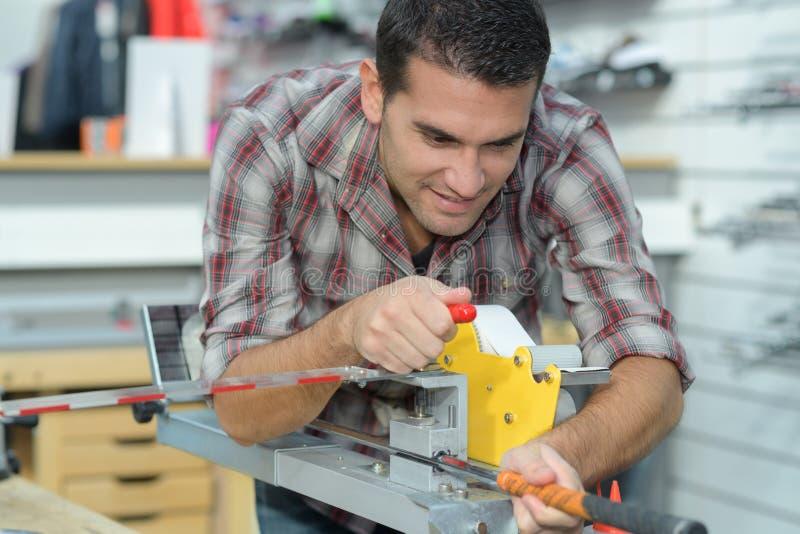 O trabalhador que verifica a qualidade processou a ferramenta usando o dispositivo ótico preciso foto de stock