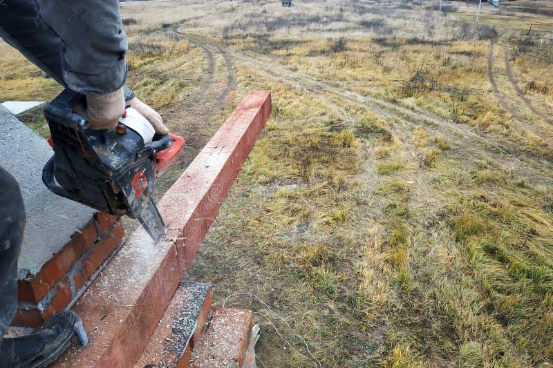 O trabalhador realiza as serras de cadeia de utilização de processamento de madeira na construção da casa imagem de stock