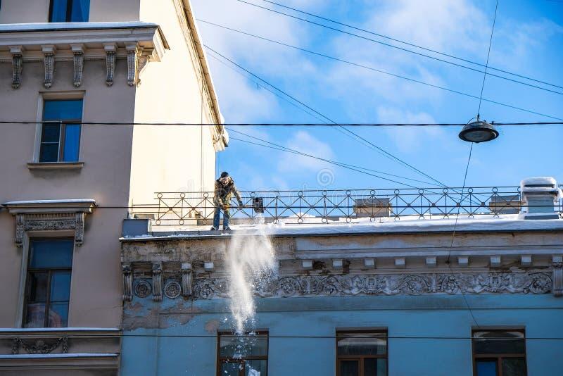 O trabalhador remove a neve do telhado imagem de stock