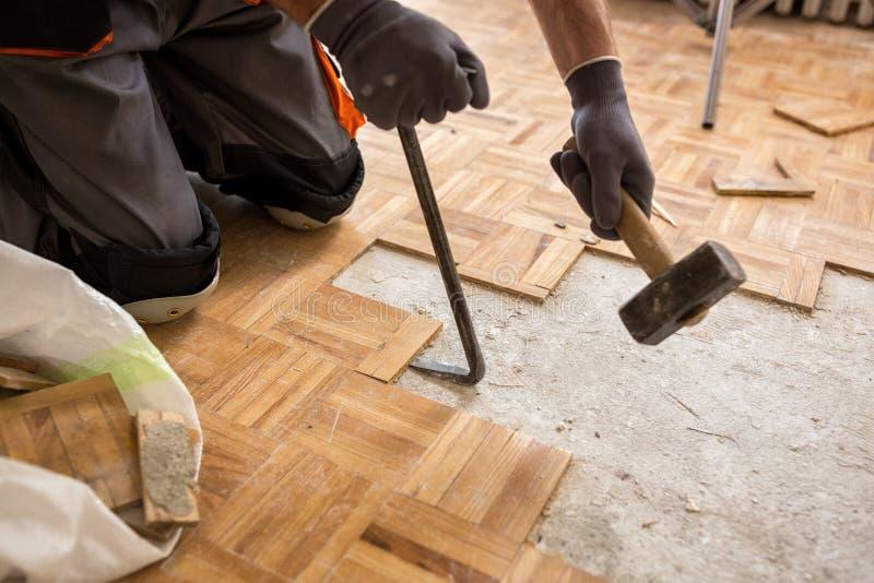 O trabalhador remove o fparquet velho, casa da renovação fotografia de stock