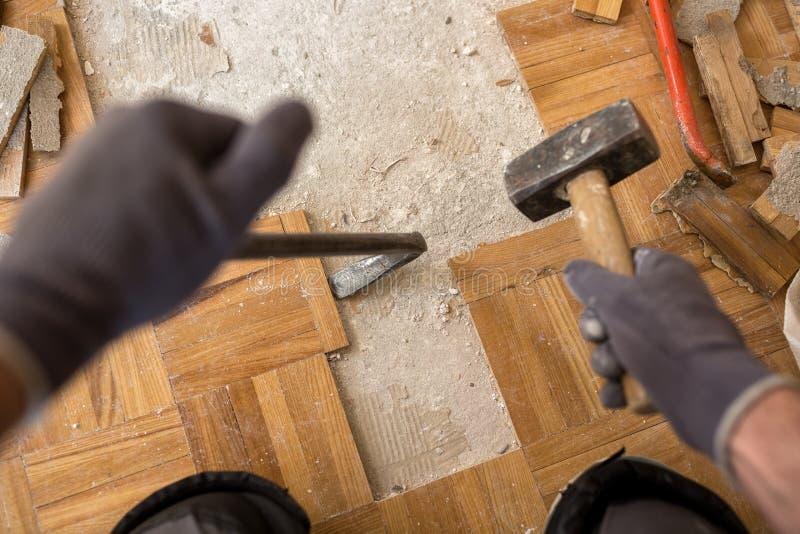 O trabalhador remove o fparquet velho, casa da renovação imagem de stock royalty free