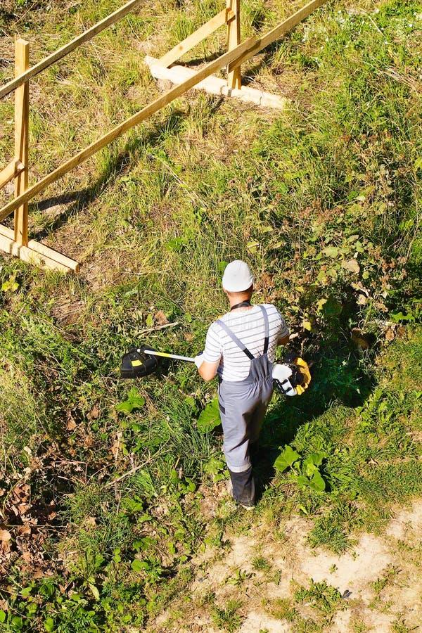 O trabalhador sega a grama Brushcutter da gasolina dos usos Perto do quadro novo da cerca da construção imagens de stock