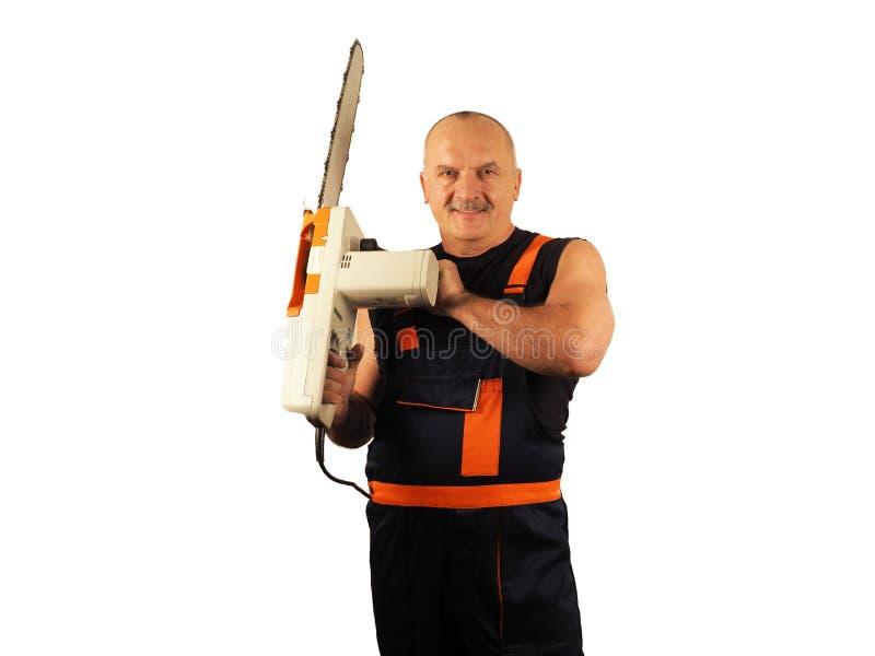 O trabalhador superior com a serra elétrica imagem de stock