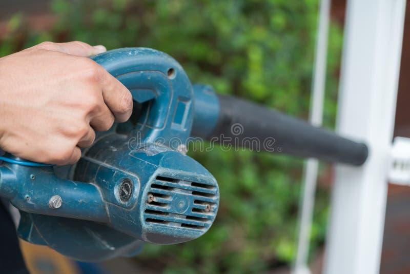 O trabalhador usa um ventilador à mão para remover a poeira foto de stock royalty free