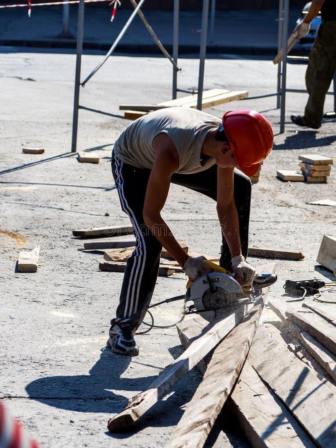 O trabalhador vê com uma serra circular na rua imagem de stock royalty free