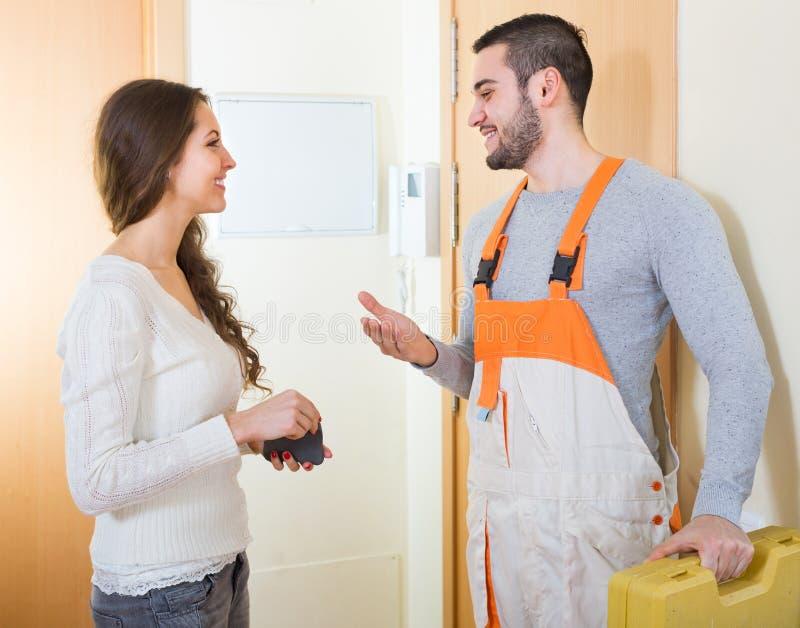 O trabalhador veio chamar a dona de casa imagem de stock
