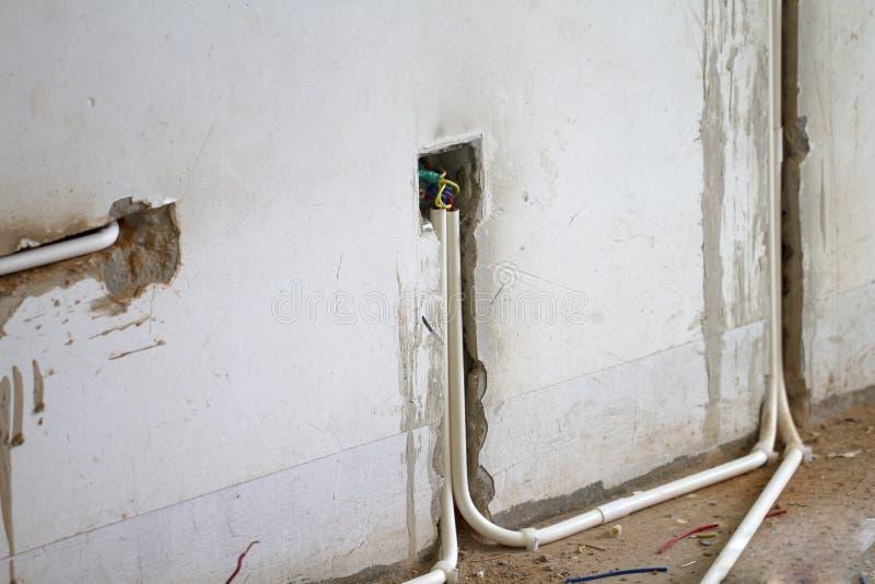 O trabalho de renovação bonde, enterra uma tubulação do pvc na parede imagem de stock