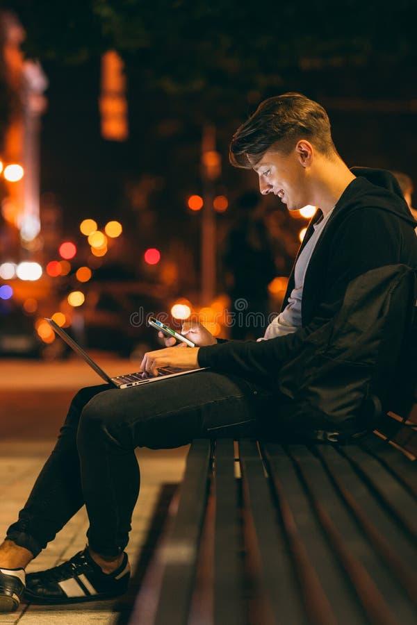 O trabalho do homem novo e comunica-se na noite fotografia de stock royalty free