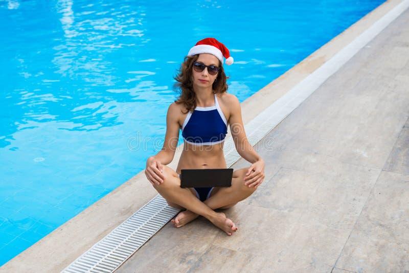 O trabalho durante os feriados, uma mulher encontra o Natal em um país tropical Jovem mulher no funcionamento do chapéu de Papai  fotografia de stock