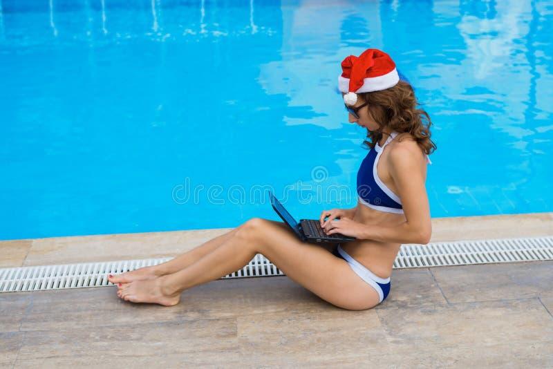 O trabalho durante os feriados, uma mulher encontra o Natal em um país tropical Jovem mulher no funcionamento do chapéu de Papai  fotos de stock royalty free