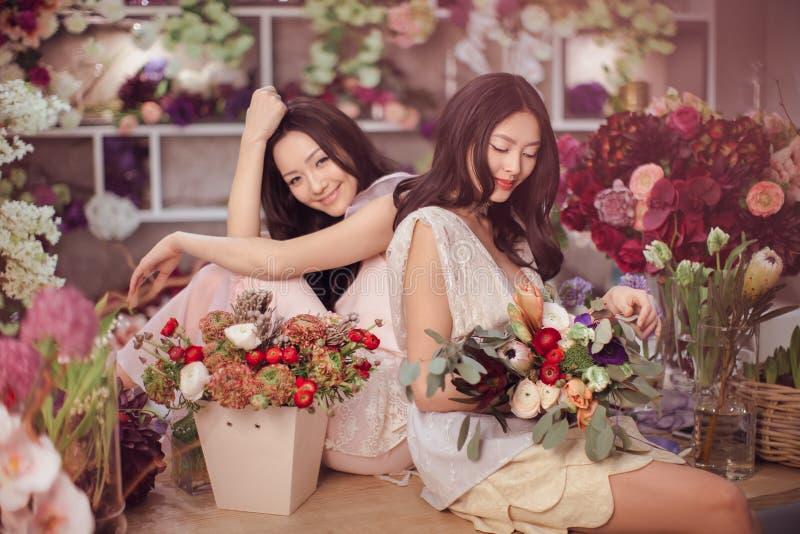 O trabalho feliz dos floristas asiáticos bonitos das mulheres na loja de flor com muita mola floresce fotos de stock