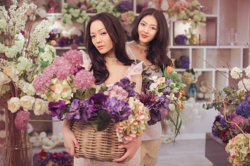 O trabalho feliz dos floristas asiáticos bonitos das mulheres na loja de flor com muita mola floresce imagens de stock royalty free