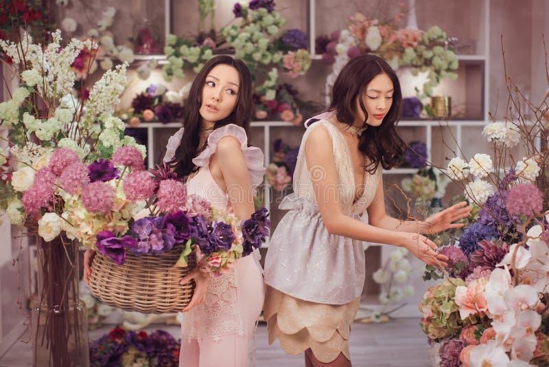 O trabalho feliz dos floristas asiáticos bonitos das mulheres na loja de flor com muita mola floresce foto de stock