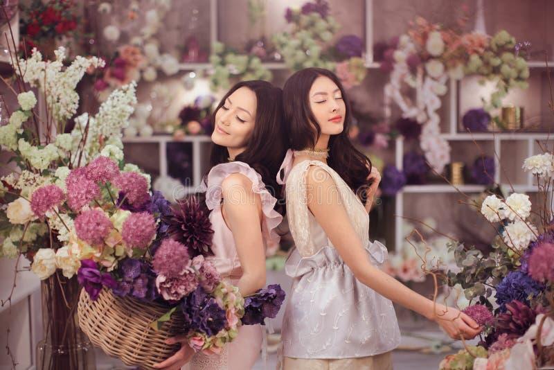 O trabalho feliz dos floristas asiáticos bonitos das mulheres na loja de flor com muita mola floresce imagens de stock