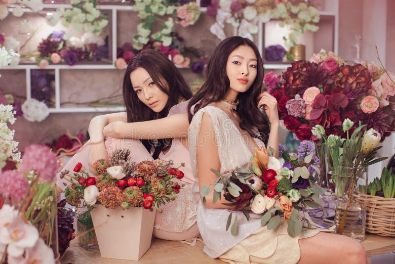 O trabalho feliz dos floristas asiáticos bonitos das mulheres na loja de flor com muita mola floresce foto de stock royalty free