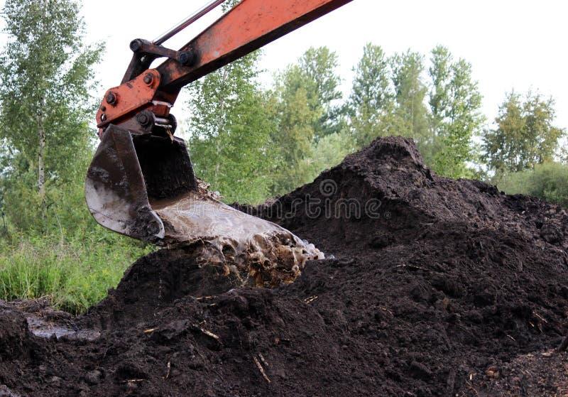o trabalho sujo da cubeta da máquina escavadora, que escava e nivelou as colheres à terra molha em reparos da estrada fotografia de stock royalty free